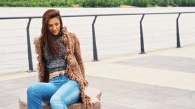 摆在在散步的石长凳的美丽的年轻女人在河在城市 股票录像