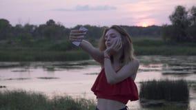 摆在在日落年轻女人背景的照相机电话的逗人喜爱的女孩在日落女性做selfie休息 股票视频