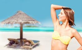 摆在在海滩的比基尼泳装的年轻女人 免版税库存照片