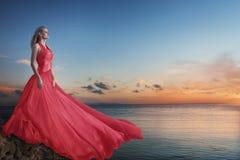 摆在在海滩的豪华长的礼服的美丽的年轻女人 库存图片