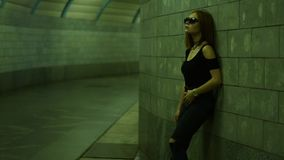 摆在地下过道的照相机的黑暗的衣裳的美丽的时髦的夫人 股票录像