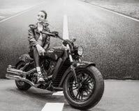 摆在坐一辆经典摩托车的美丽的女孩骑自行车的人 图库摄影