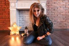 摆在坐地板的黑皮夹克的女孩 免版税库存图片