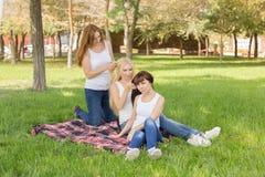 摆在坐格子花呢披肩的美丽的女孩在公园 库存图片