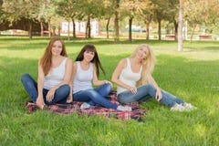 摆在坐格子花呢披肩的美丽的女孩在公园 图库摄影