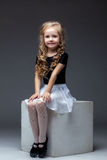 摆在坐立方体的微笑的逗人喜爱的女孩在演播室 免版税库存图片