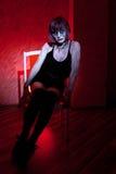 摆在坐红色的吸血鬼女孩 免版税库存图片