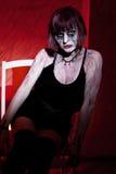 摆在坐红色的吸血鬼女孩 免版税图库摄影