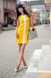 摆在城市街道上的美丽的女孩 免版税库存照片