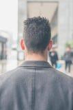 摆在城市街道的后面观点的一个年轻人 免版税图库摄影