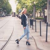 摆在城市街道的美丽的女孩 免版税库存图片