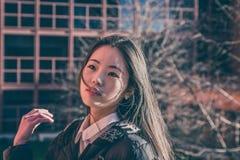 摆在城市街道的年轻美丽的中国女孩 库存照片