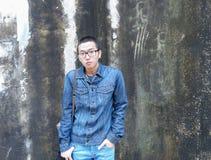 摆在墙壁上的英俊的亚裔偶然牛仔裤玻璃人有地衣背景 年轻韩语画象对土混凝土墙 库存照片