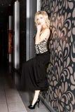 摆在墙壁附近的一条长的黑裙子的美丽的少妇 免版税库存照片