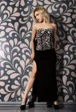 摆在墙壁附近的一条长的黑裙子的美丽的少妇 库存照片