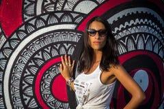 摆在墙壁附近的白色T恤杉的年轻地中海女孩 免版税库存照片