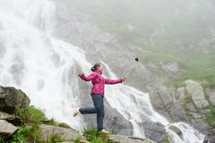摆在壮观的Balea瀑布前面的岩石的微笑的年轻女性制造的selfie在罗马尼亚 图库摄影