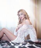 摆在复杂的室内停留在床上的白色女用贴身内衣裤的年轻美丽的性感的妇女。有吸引力的性感的白肤金发的佩带的女用贴身内衣裤 库存图片