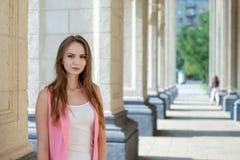 摆在夏天城市街道的年轻美丽的时髦的女孩在一个晴天 免版税图库摄影