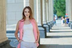 摆在夏天城市街道的年轻美丽的时髦的女孩在一个晴天 库存照片