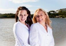 摆在夏天太阳的母亲和女儿 免版税库存照片