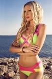 摆在夏天海滩的明亮的比基尼泳装的性感的白肤金发的妇女 免版税库存照片