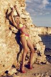 摆在夏天海滩的比基尼泳装的性感的白肤金发的妇女 库存图片