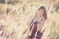 摆在夏天的白种人女孩在领域的日落 免版税库存照片