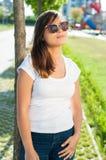 摆在外面在公园的俏丽的女孩在阳光下 免版税图库摄影