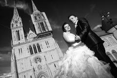 摆在大教堂前面的新婚佳偶黑白 免版税库存图片
