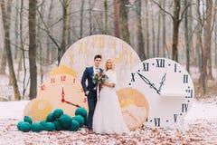 摆在大葡萄酒的愉快的婚礼夫妇在秋天森林创造性的装饰计时 图库摄影