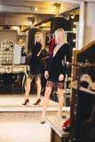 摆在大镜子的礼服的年轻白肤金发的妇女 库存照片