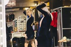摆在大镜子的礼服的年轻白肤金发的妇女 免版税库存照片