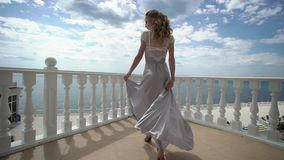 摆在大阳台的女用贴身内衣裤的年轻白肤金发的妇女有海视图 影视素材