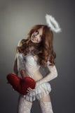 摆在天使服装的微笑的红发秀丽 免版税库存图片