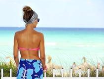 摆在天堂海滩的桃红色比基尼泳装的愉快的年轻可爱的妇女 库存图片