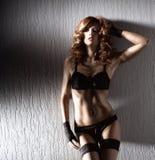 摆在女用贴身内衣裤的一名新和性感的红头发人妇女 免版税库存照片