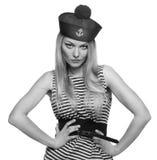 摆在她的制服的白肤金发的女性水手 库存图片
