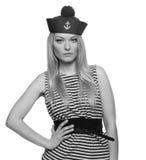 摆在她的制服的白肤金发的女性水手 免版税库存图片