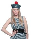摆在她的制服的年轻白肤金发的女性水手 库存图片
