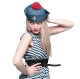 摆在她的制服的年轻白肤金发的女性水手 免版税库存照片