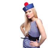摆在她的制服的年轻白肤金发的女性水手 免版税库存图片