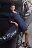 摆在她的汽车旁边的秀丽妇女 库存照片