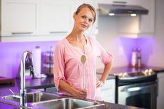 摆在她的现代厨房里的俏丽,少妇 免版税库存照片