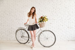 摆在她的老减速火箭的自行车旁边的女孩 免版税库存图片