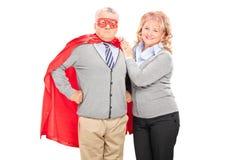 摆在她的超级英雄丈夫旁边的成熟夫人 免版税图库摄影