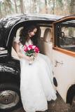 摆在她的除草天的减速火箭的汽车的愉快的新娘 图库摄影