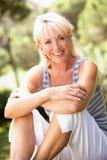 摆在妇女的年龄中间公园 免版税库存照片