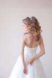 摆在婚礼发型和礼服的美丽的新娘 库存照片