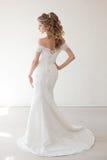 摆在婚礼发型和礼服的美丽的新娘 免版税库存图片